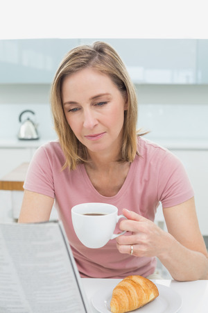 Concentrated woman reading newspaper while having coffee in the kitchen at home photo