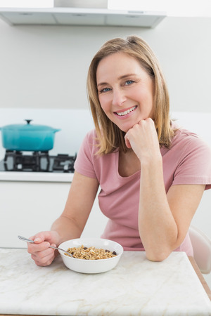 mature adult women: Portrait of a smiling woman having cereals in the kitchen at home