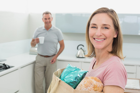 Portrait of a woman carrying grocery bag while man with coffee cup in the kitchen at home photo