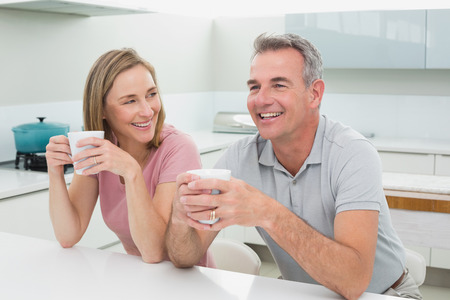 Happy relaxed couple with coffee cups in the kitchen at home photo