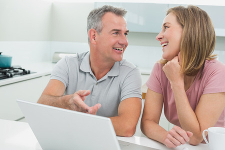 Cheerful couple in conversation while using laptop in the kitchen at home photo