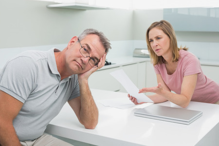 Unhappy couple having an argument over a bill in the kitchen at home