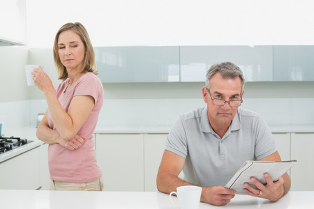 Displeased woman drinking coffee while man reading newspaper in the kitchen at home photo