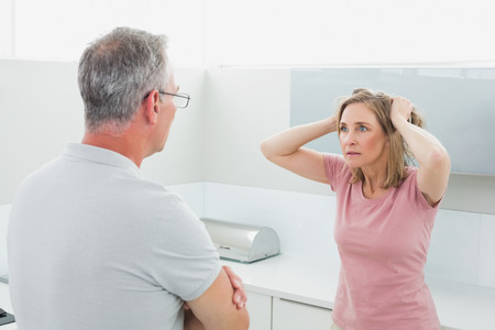 Unhappy couple having an argument in the kitchen at home photo