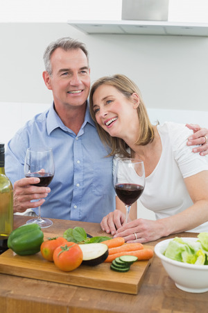 Loving couple with wine glasses in the kitchen at home photo