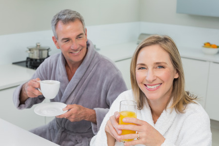 Portrait of a smiling couple with orange juice and coffee in the kitchen at home photo