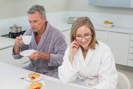 Couple in bathrobes having breakfast in the kitchen at home photo