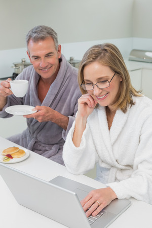 Couple in bathrobes having breakfast while using laptop in the kitchen at home photo