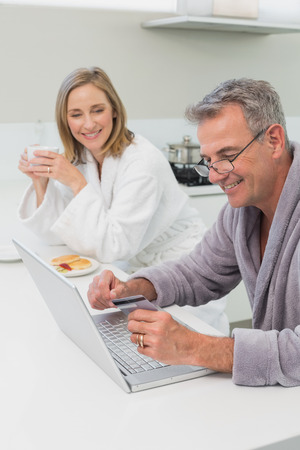 Happy couple in bathrobe doing online shopping through laptop and credit card at home photo