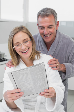 Happy couple in bathrobes reading newspaper in the kitchen at home photo