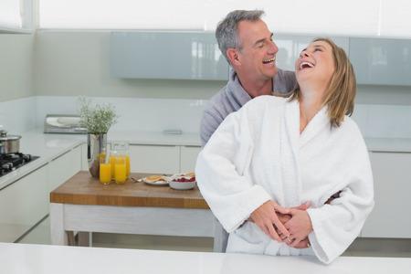 mujer de espaldas: Sonriente hombre abarca mujer alegre por detr�s en la cocina en el hogar Foto de archivo