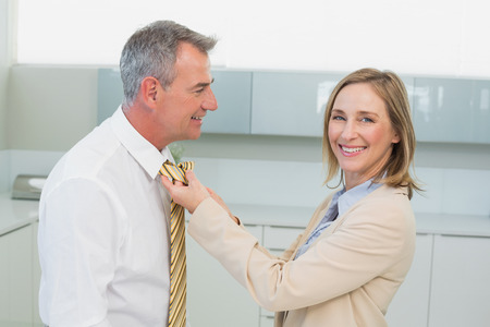 Side view of a woman adjusting businessmans tie in the kitchen at home Stock Photo