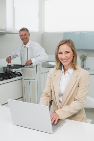 Portrait of a smiling businesswoman using laptop while man preparing food in the kitchen at home photo