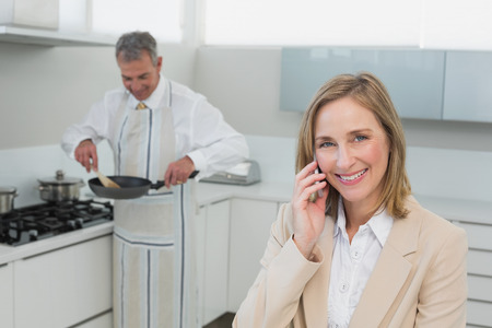 Businesswoman on call while man preparing food in the kitchen at home photo