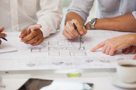 architect office: Close-up mid section of business people working on blueprints in the office