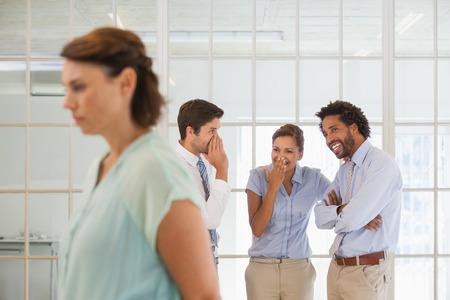 acoso laboral: Colegas que chismean con joven empresaria triste en primer plano en una oficina brillante