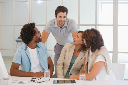 Group of young business people having a conversation at office desk photo