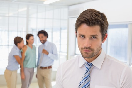 Colleagues gossiping with sad young businessman in foreground at a bright office photo