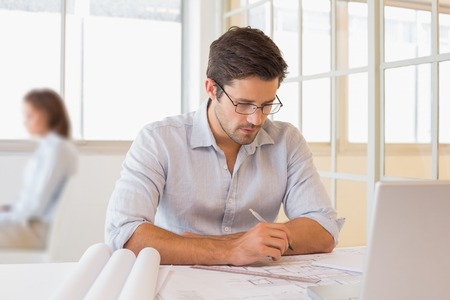 asian architect: Concentrated young businessman working on blueprints in the office Stock Photo