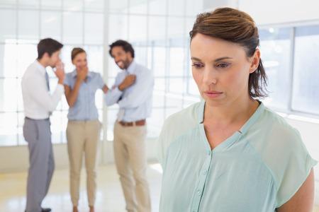 acoso laboral: Colleauges cotilleando con joven empresaria triste en primer plano en una oficina brillante