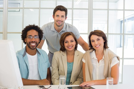 Portrait of young business people smiling at office desk photo