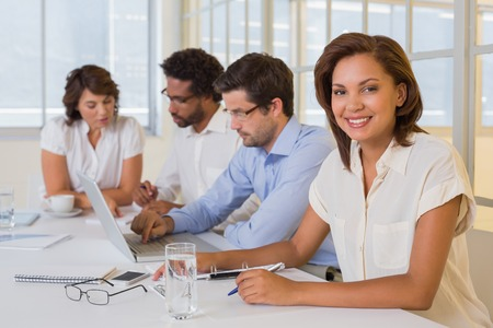 Portrait of a smiling businesswoman with colleagues in meeting at the office photo