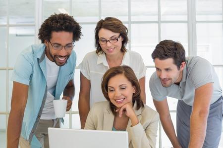 若いビジネス人のオフィスで一緒にノート パソコンを使用しての笑顔のグループ