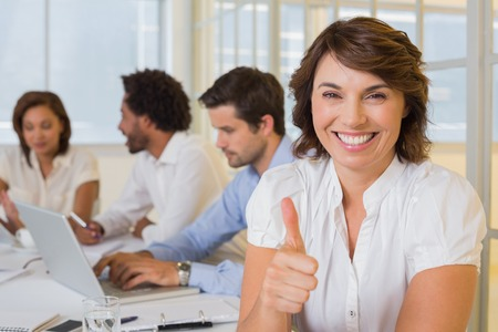 Portrait of a smiling businesswoman gesturing thumbs up with colleagues in meeting at the office photo