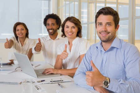 thumbs up gesture: Portrait of happy business people gesturing thumbs up in meeting at the office