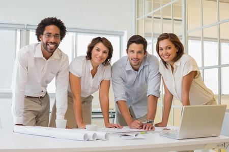 オフィスでの青写真に取り組んで幸せな若いビジネス人々 の肖像画