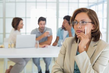 Close-up van een ernstige onderneemster met collega's in vergadering op achtergrond op het kantoor