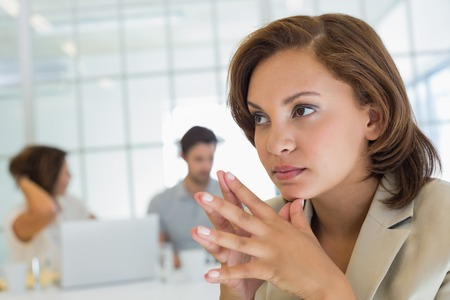 thinking woman: Close-up of a serious businesswoman with colleagues in meeting in background at the office Stock Photo