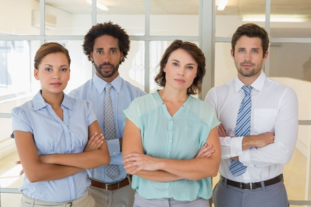 unsmiling: Group portrait of serious young business people in the office