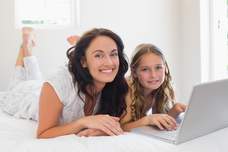 Portrait of mother and daughter with laptop lying in bed at home photo