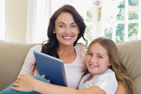 Portrait of happy mother and daughter with digital tablet sitting on sofa at home photo
