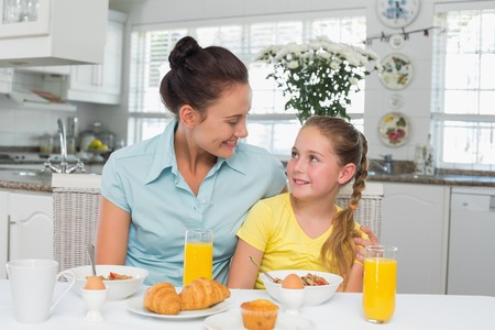 Cute girl looking at mother while having breakfast in house photo