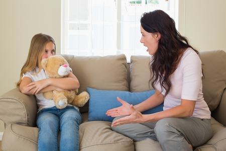 brown hair: Angry mother shouting at daughter while sitting on sofa at home
