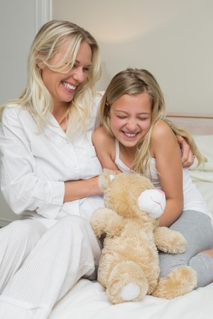 tickling: Happy mother tickling daughter while sitting in bed at home
