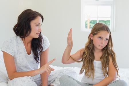 집에서 침대에 앉아있는 동안 화가 어머니에게 그만 제스처를 보여주는 어린 소녀
