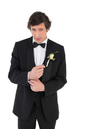Portrait of handsome groom in tuxedo getting ready over white background Stock Photo - 28043275