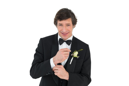 Portrait of smiling groom in tuxedo getting ready over white background Stock Photo - 28043276