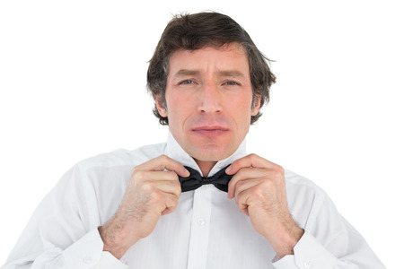 corrects: Portrait of handsome groom corrects bow tie over white background