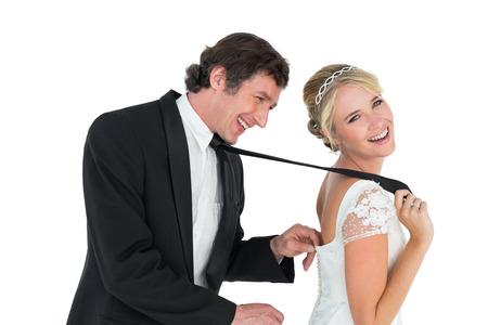 Playful newlywed couple over white background photo