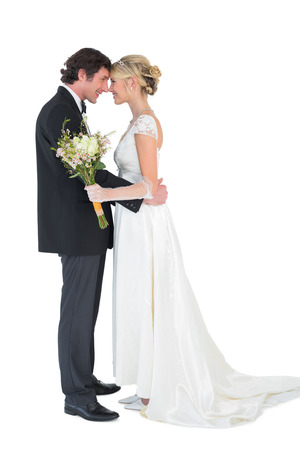 Profile shot of loving bride and groom with head to head over white background photo