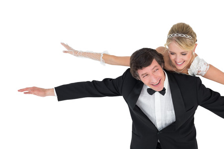 Portrait of playful newly wed couple with arms outstretched over white background photo