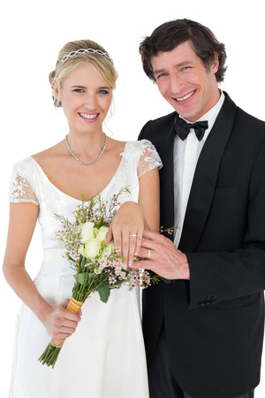 Portrait of happy bride and groom showing wedding rings isolated over white background photo