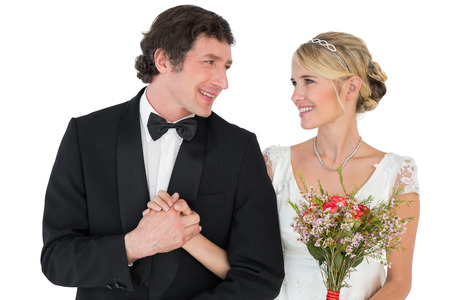 Happy bride and groom holding hands while looking at each other over white background photo