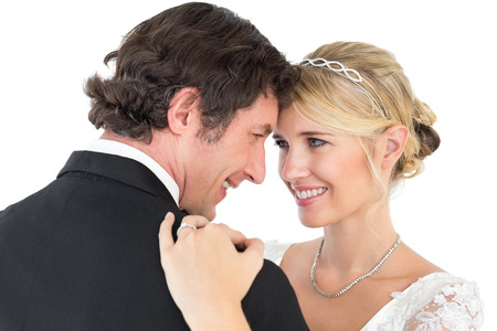 Happy bride and groom embracing while looking at each other over white background photo