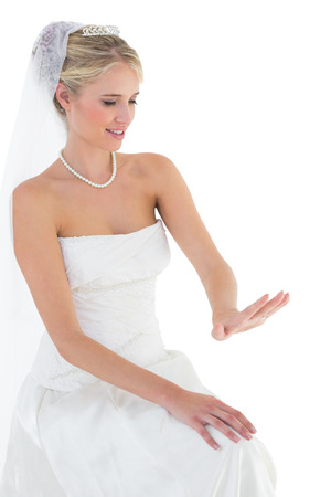 off the shoulder: Smiling bride in off shoulder dress looking at wedding ring over white background Stock Photo