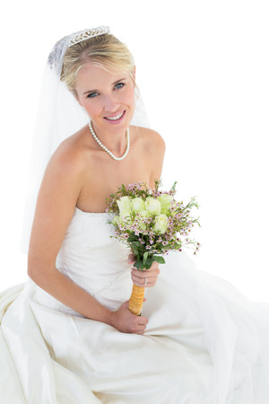 off the shoulder: Portrait of beautiful bride holding flower bouquet while sitting over white background